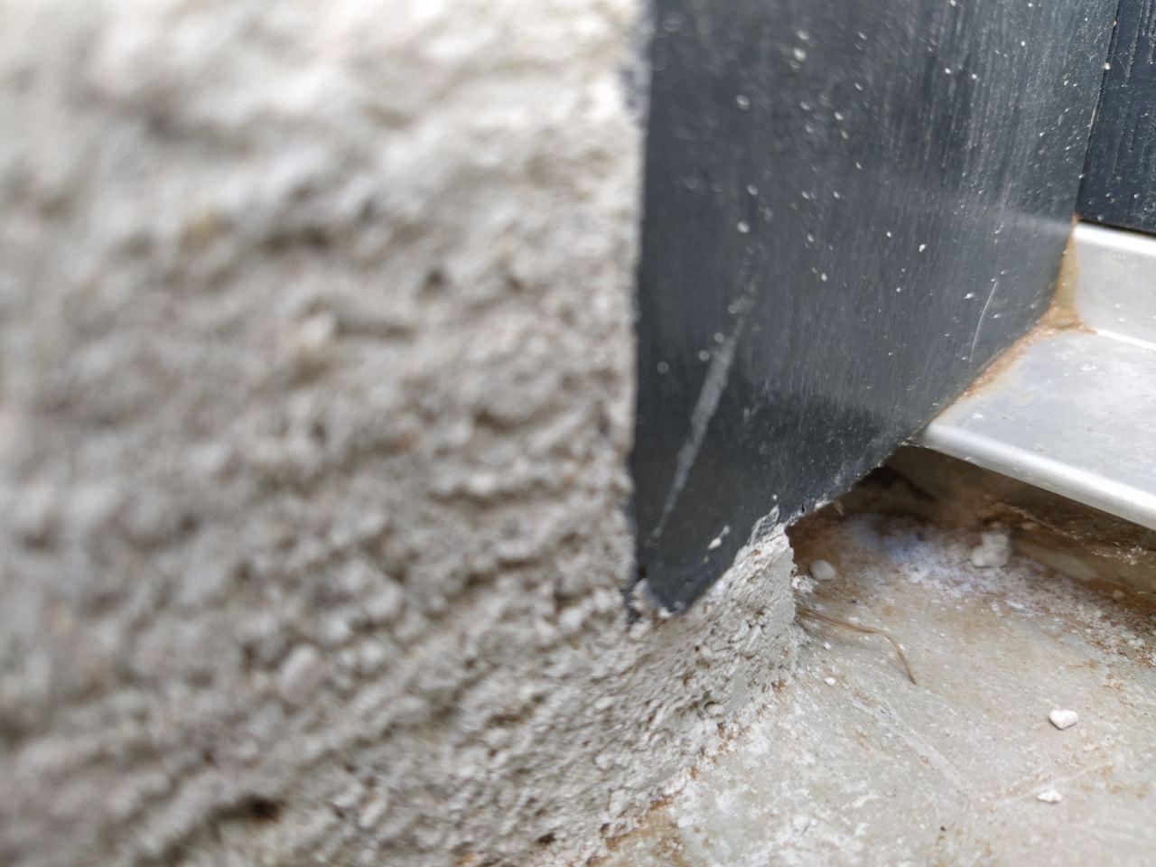 Partie basse de la porte d'entrée côté extérieur : Petit trou entre le seuil en alu et la partie inférieure en béton. La finition laisse à désirer.