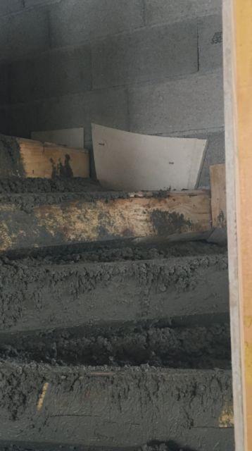 Pose des rupteurs de pont thermique à chaque marche qui s'appuie sur le mur.
