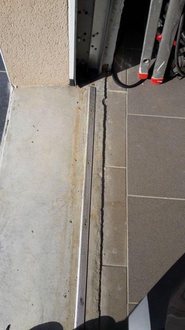 Solution pour éviter l'eau de pluie sous porte de garage. <br /> Une cornière de seuil alu juste derrière le joint de porte