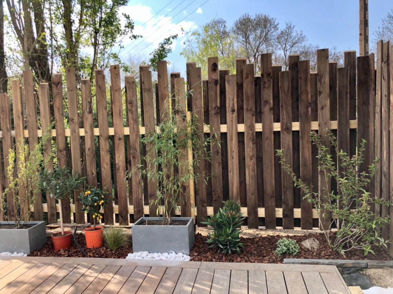 Clôture maison fait avec des lames de terrasses et plantation le long