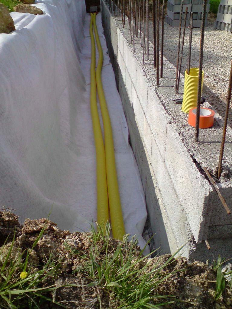 Pose de deux drains, une partie du mur est enduite pour étanchéité (futur garage)