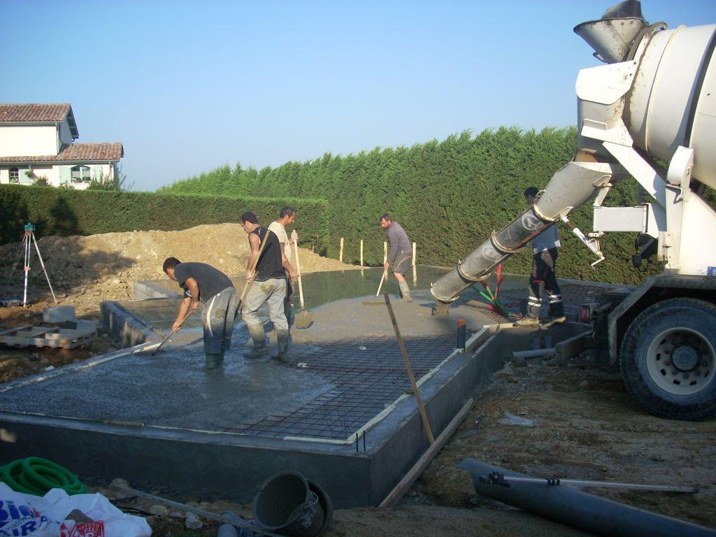 Epandage du ciment. Les maçons en pleine action.