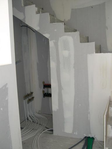Placard sous escalier qui acceuille les tuyaux pour les réglages des tuyaux pour le plancher chauffant...