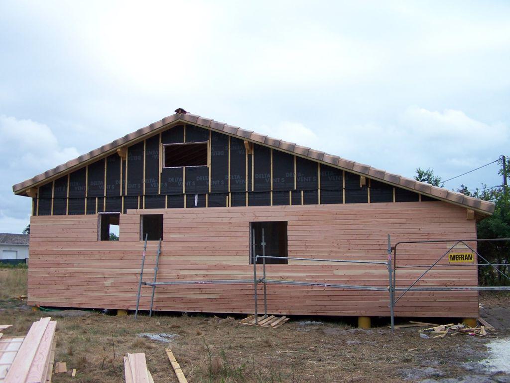 Le bardage en douglas non traité est en cours de pose (façade nord de la maison).