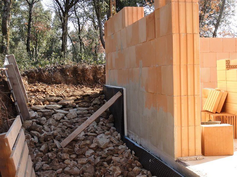 Remblai vide sanitaire et de la différence de niveau avec le terrain voisin (80 cm), ce ne sont pas les cailloux qui manquent...