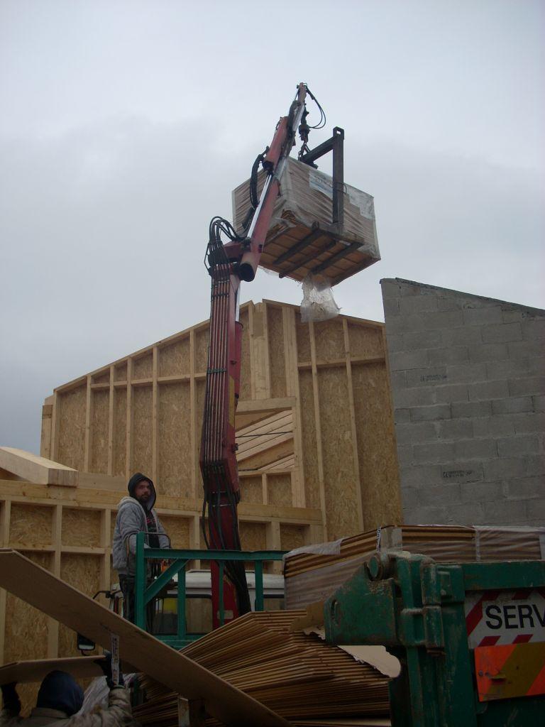 Cedric monte la fibre de bois sur le toit.