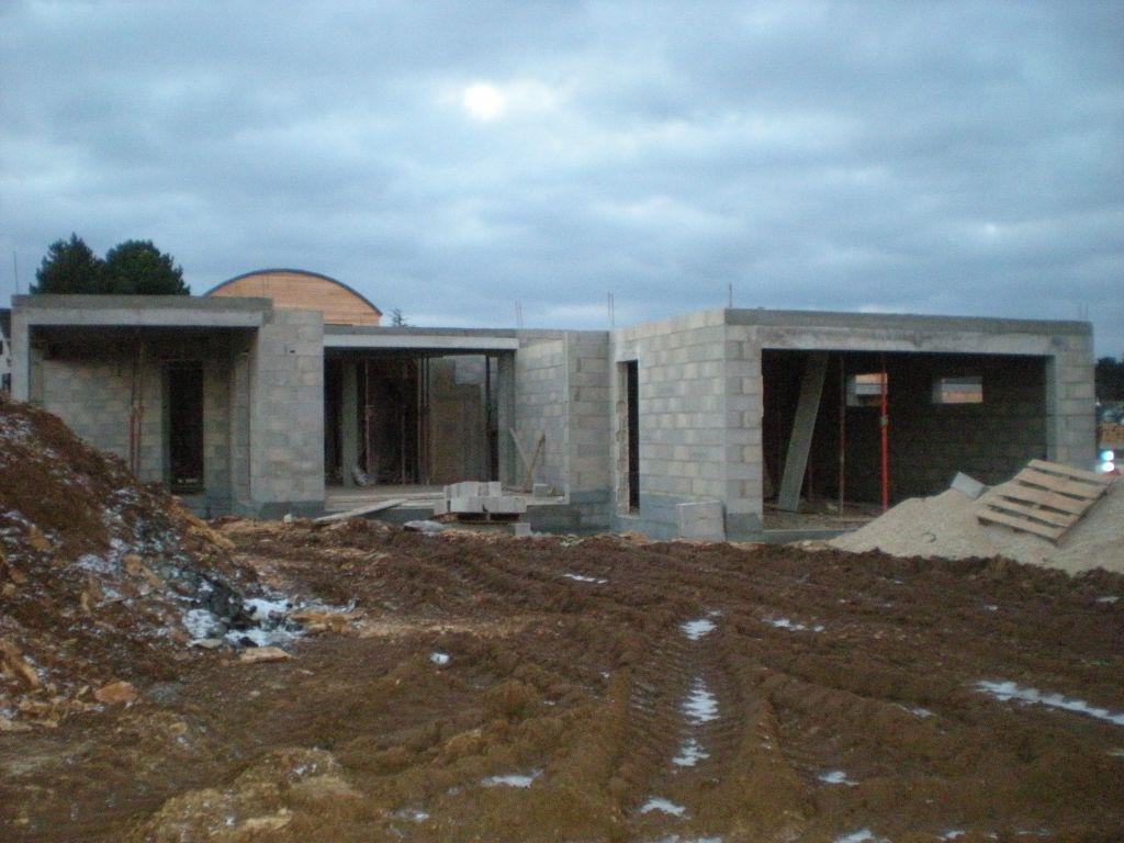 RDC terminé, vue est : terrasse à gauche, baie au centre et garage à droite
