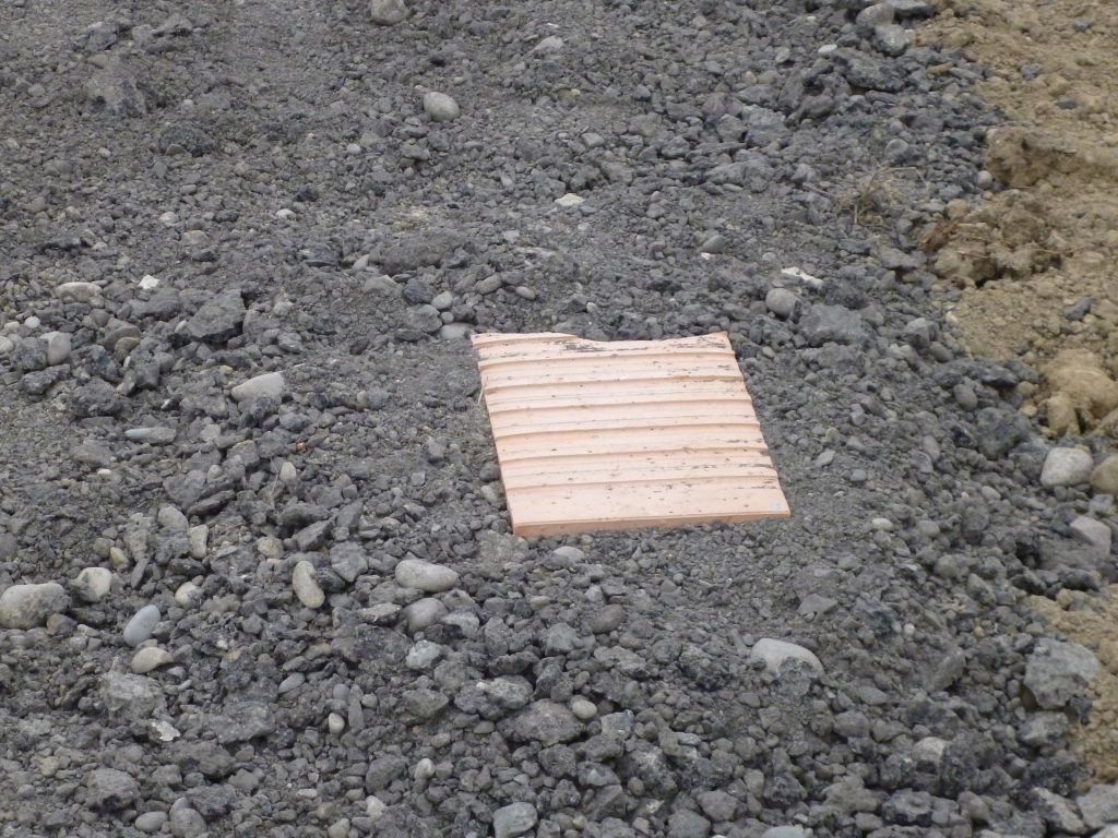Brique sur chemin d'accès posée pour indiquer la hauteur finale du remblai (plot de niveau)