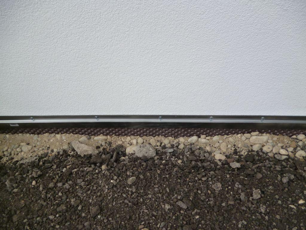 Profilé de finition du Delta-MS posé sur mur de la maison avant remblaiement