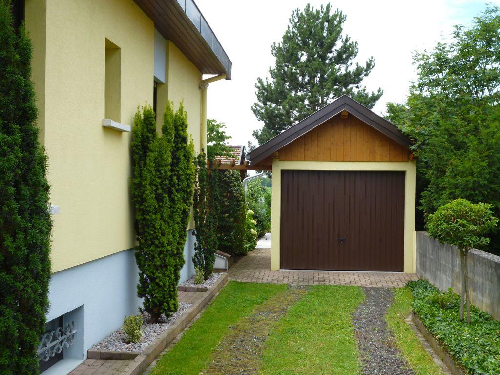 Arrivée devant le garage pour emprunter le passage menant au jardin et potager