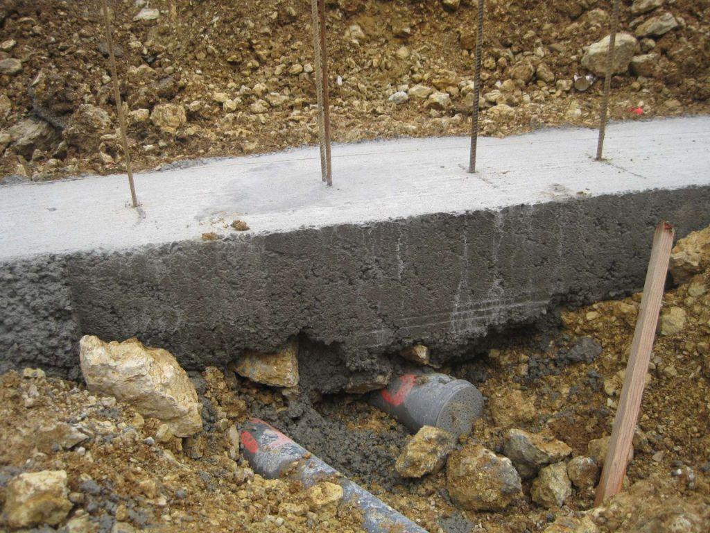 Canalisations d'eau pluviale et d'eau usée sous les fondations