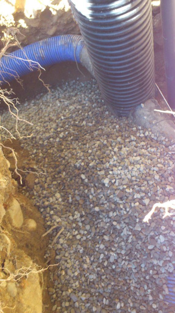 """Début du remblayage du regard, la gaine est a 1.80 du sol, pas pu faire mieux avec cette pelleteuse - et en plus elle a déchenillée...L'angle en haut a été un peut """"adouci"""". On voit sur la droite le drain du trop plein des cuves à eau de pluie, auquel je raccorderais la vidange de la pompe -et oui encore une - d'aspiration des condensats de la gaine Hegler."""