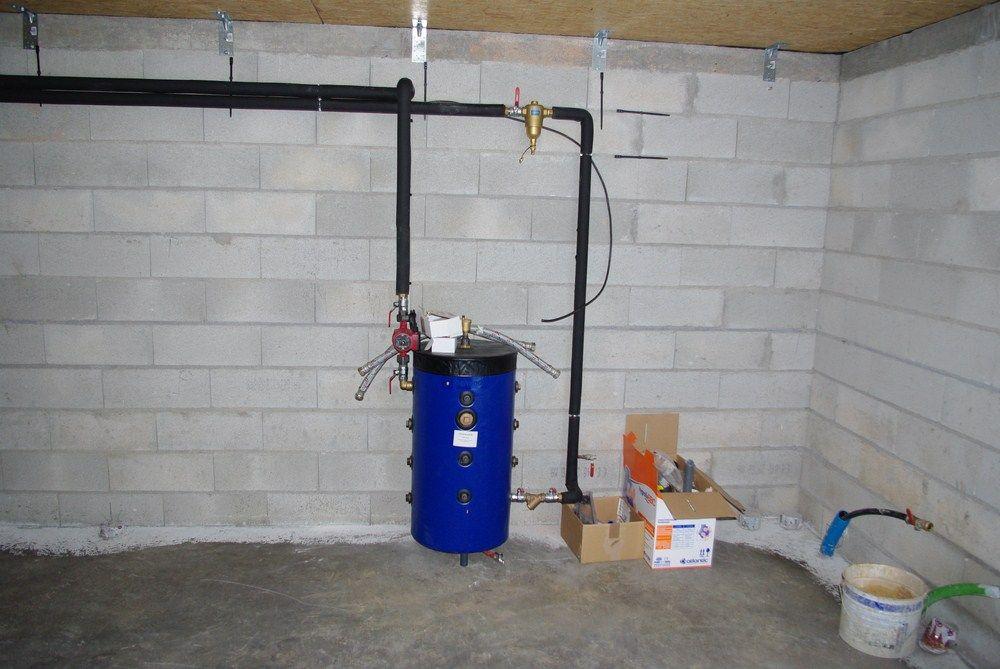 Installation du ballon tampon relié à la pompe à chaleur, elle-même située à l'extérieur.