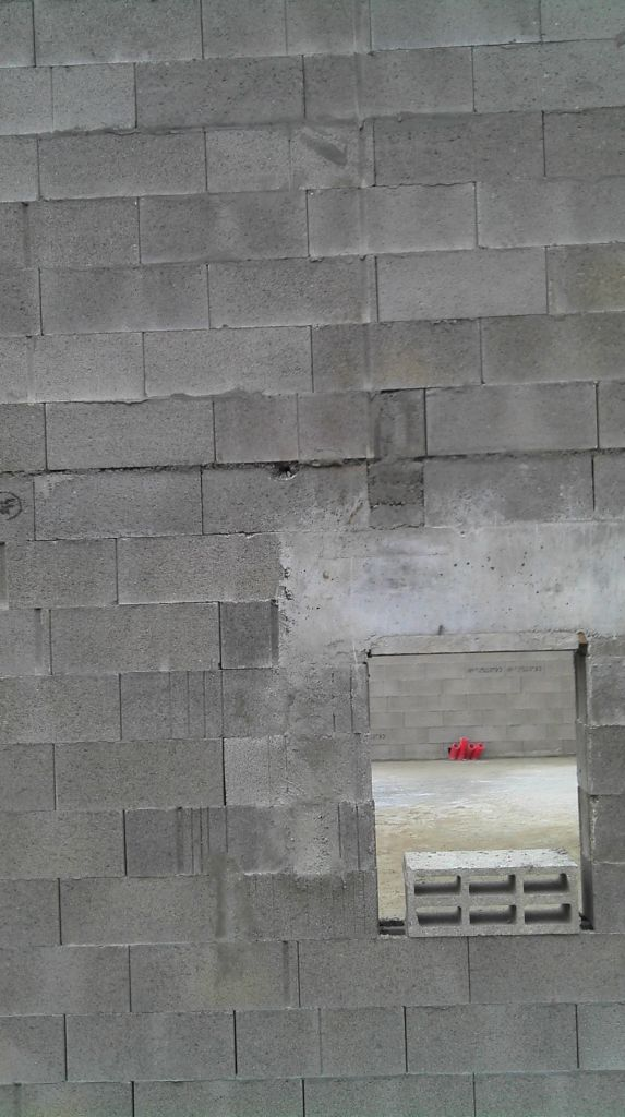 trou dans le parpaing en haut à gauche de la fenêtre qui le traverse de part en part