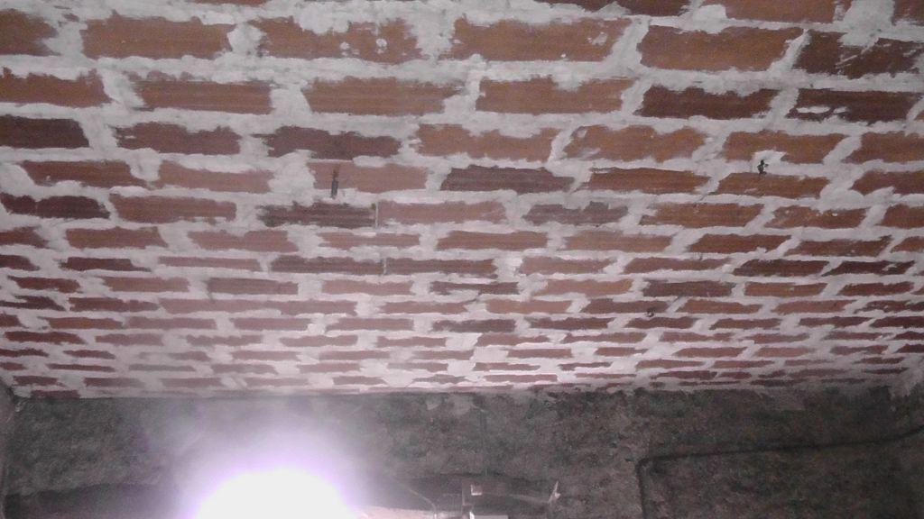 Un plafond en brique rouge suspendu aux poutres par des fils de fer!