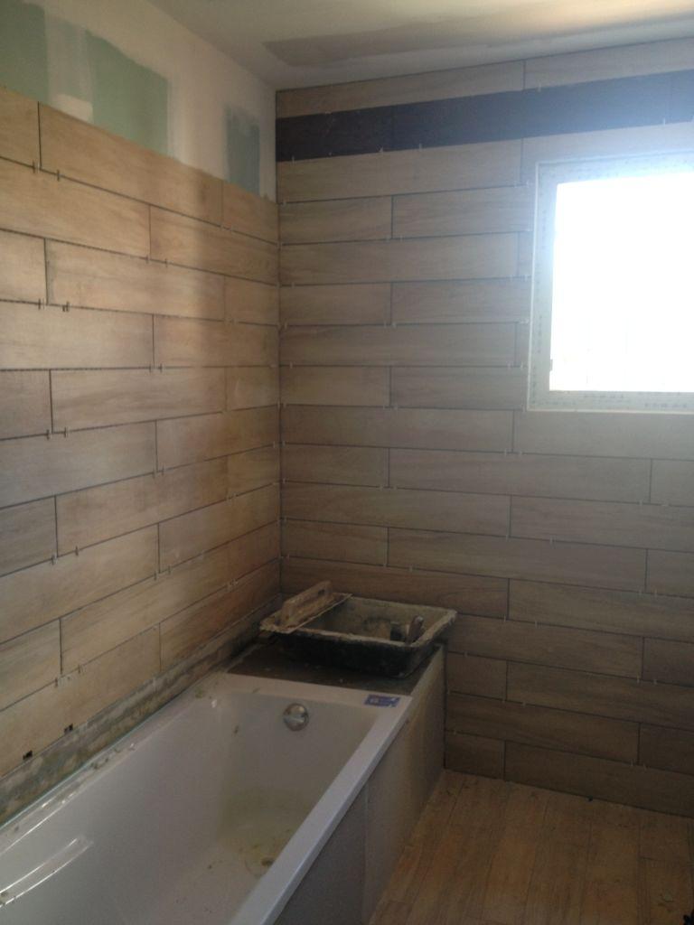 Pose de la faïence imitation bois, la baignoire va recevoir un habillage couleur chocolat mais toujours en imitation parquet