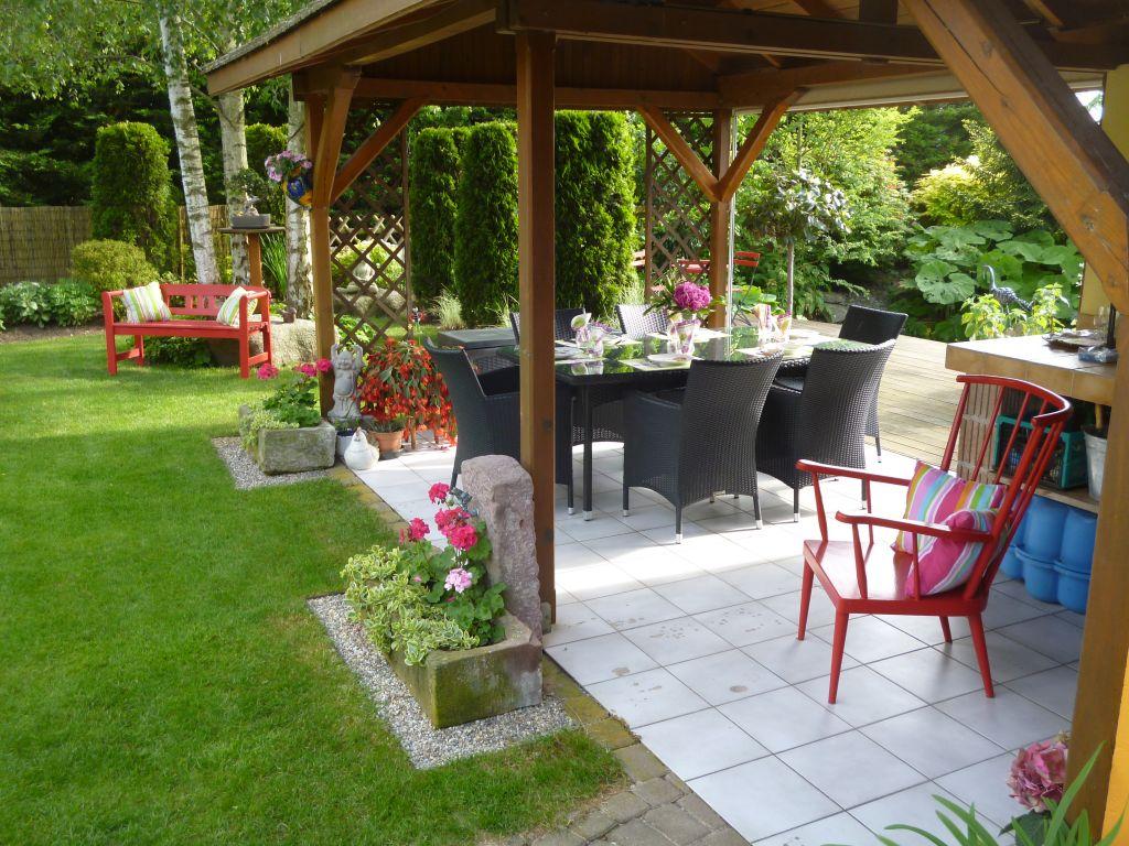 Table mise pour une soirée BBQ avec banc et chaise rouges habillés de coussins multicolores. Bon appétit !!!!!