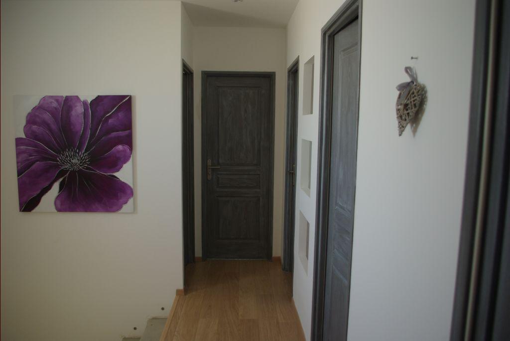 couloir a l?étage avec les porte peinte en grise avec du lasuré blanc