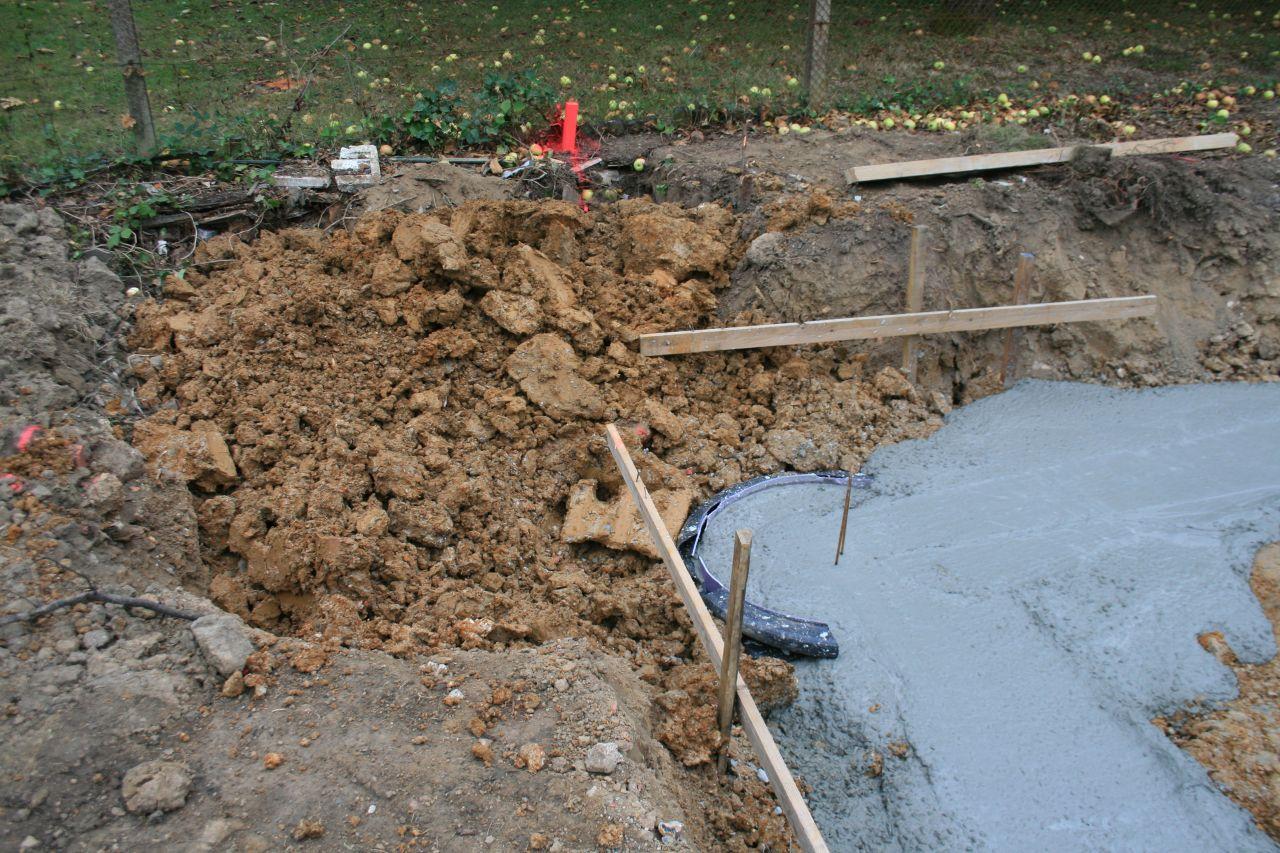 Le même trou avec les fondations coulées. Un poteau a été ajouté (on voit le gabarit en plastique utilisé pour le moulage) qui va chercher la terre dure en dessous du niveau de la cuve.