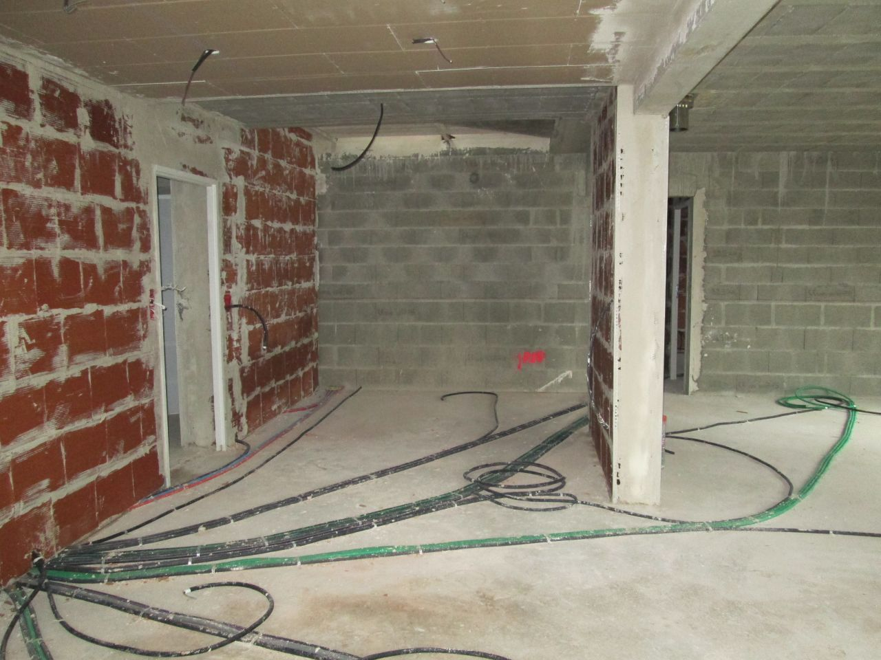 Emplacement de l'escalier au fond, sur le mur de parpaing, vu de la cuisine. <br /> La porte de gauche donne dans le scellier.