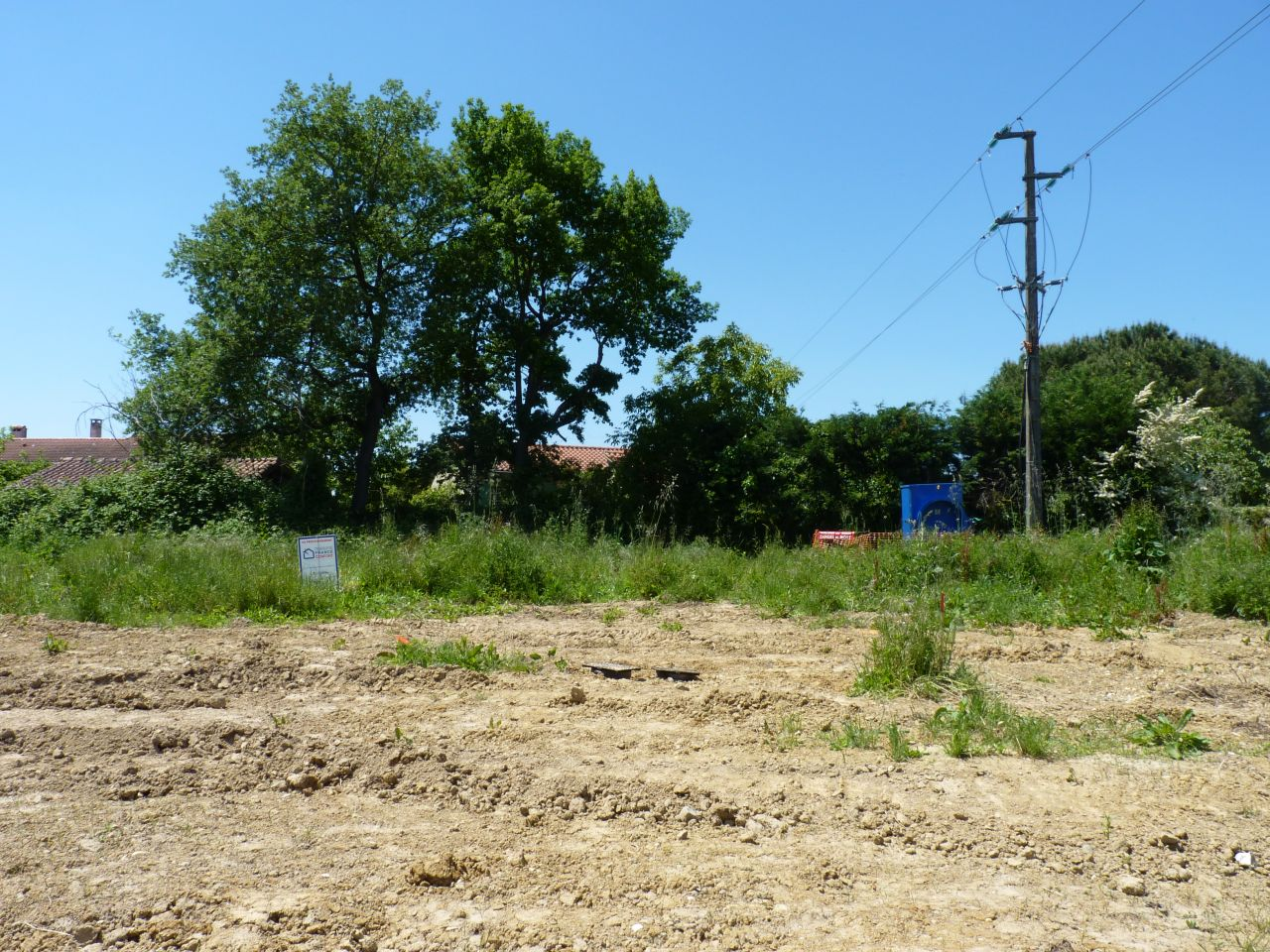Sur cette photo, à gauche là ou sera ma maison (mon garage sera à peu près au niveau du panneau). Le grand box EDF sera la limite séparative avec mon voisin du lot 17. La ligne électrique juste au dessus sera enterrée et la bande de terre sera une servitude EDF appartenant à mon voisin du 17.
