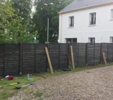 La clôture est en place, les étais sont là pour maintenir les panneaux bien verticaux pendant la prise du béton (les pieds sont enfoncé de 50 cm dans la terre et scellés dans du béton sur 20 cm de haut)