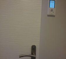 Portes interieures effet mini vagues et à côté, le gestionnaire d'énergies à detecteur de mouvements.