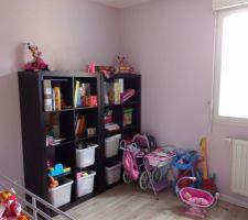 meuble a jouets de la petite avec en fond peinture rose paillette