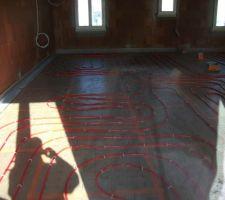 Installation des tuyaux en vue du plancher chauffant.