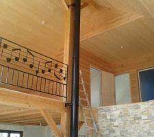 vue du salon sur la mezzanine balcon chemina e mur en pierre de parement et bardage bois douglas pour les cloisons et sapin pour mezzanine