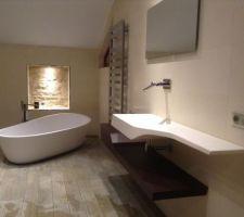 Vue d'ensemble, avec niche en pierre, baignoire en Krion 180 / 95 avec robinetterie sur pied cascade Lounge et meuble lavabo Spirit