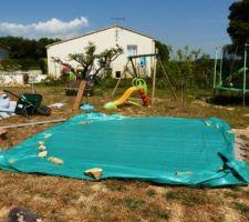 ZE piscine - on prépare le terrain:puis on a posé une bâche plié en eux par-dessus le sable pour protéger la piscine...