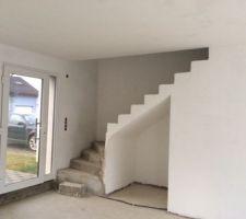 montee d escalier qui sera habillee d un carrelage taupe et la porte vitree d entree