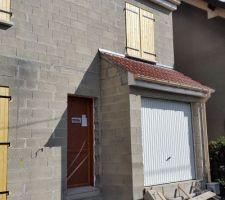 Volets, porte d'entrée et porte de garage posés. Nous peindrons les volets et la porte d'entrée en blanc.