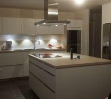 C'est une cuisine en blanc strié avec un plan de travail imitation bois clair.