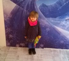 La petite qui pose tout heureuse devant son poster