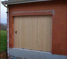 Porte de garage en bois (pas encore peinte) coulissante le long du mur avec partie indépendante permettant de n'ouvrir qu'une petite partie comme une simple porte.