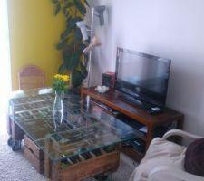 Table basse faite maison avec casier à bouteilles, plan de travail en verre d'un bureau, roulettes. Lampe tri-spots
