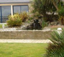 Pour notre terrain pentu, une idée de fontaine possible ( vu en Bretagne ) Celle-ci est composée, au fond, d'un escalier de pierres plates Sans parler du muret, à imaginer à ras du sol !
