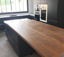 la cuisine avec son plan de travail dekton autour de l evier et de la plaque de cuisson et la table en bois de 2 4m