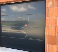 porte de garage sectionnelle belm ral 7016 on distingue les inserts argentes horizontaux qui rappelleront ceux de la porte d entree le plastique de protection n est que parcellement defait