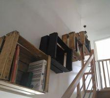 pour recuperer l espace perdu entre le mur et l escalier on a decide d installer une bibliotheque suspendue avec des caisses a pomme apres poncage vernis et peinture on adore le resultat