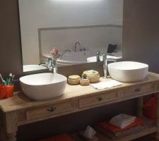 Table de drapier transformée en meuble de salle de bain pour acceuillir 2 vasques en procelaine. Le miroir est fixé sur l'arrière de la tête de lit.