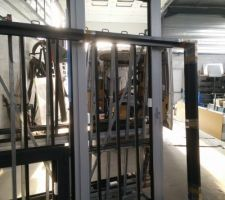 Un petit tour à l'usine du menuisier => Une porte fenêtre bicolore et une baie fixe attendent attendent leurs verres