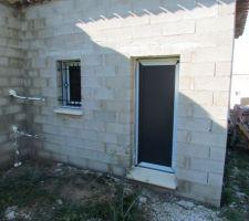 Porte de service et fenêtre du garage.