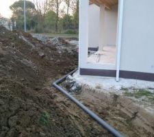 Réseau de récupération des eaux de pluie : les canalisations sont amenées vers l'arrière de la maison, vers une cuve de décantation puis vers le puits.
