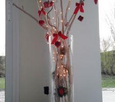 Vase garni de bois flotté et branches lumineuses.