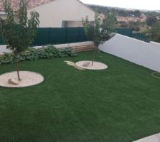 Jardin actuel avec la coulée de sable sur le gazon synthétique et les rigoles sous le gazon...