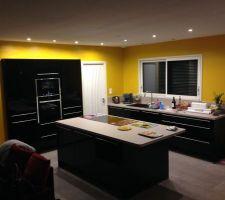 premiere partie de la cuisine posee reste les plinthes la prise electrique integree dans le plan de travail de l ilot et la hotte encastree dans plafond tout cela prevu pour demain