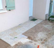 Pose de dalles gravillonnées, devant la maison : Pose des premières dalles sur un lit de sable..